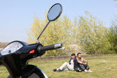 Couple sat near scooter — Stock Photo