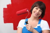 Woman painting wall red with roller — Stock Photo