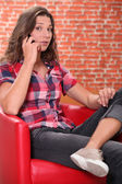 žena seděla na kožené křeslo mluvčího na mobilním telefonu — Stock fotografie