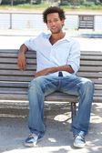 Young man sitting on a riverside bench — Stock Photo
