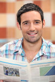 Usmívající se muž čtení novin — Stock fotografie