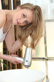 Young woman using a hairdryer — Stock Photo