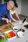 Couple preparing vegetables and looking at a laptop — Stock Photo