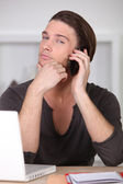 Casually dressed young man using a cellphone at his laptop — Stock Photo