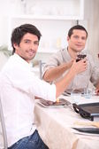 Men clinking their glasses at table — Stock Photo