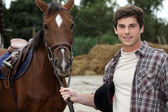 Man stood by brown horse — Stock Photo