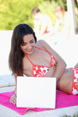 Woman in bikini using laptop — Stock Photo