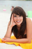 Young woman lying on a beach towel — Stock Photo
