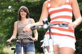 Junge frauen, die reiten fahrräder — Stockfoto
