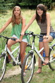 Two teenage girls riding bikes in countryside — Stock Photo