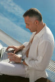 Middle-aged gentleman sitting on swimming pool edge with laptop — Stock Photo