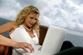 Woman sat at the coast with laptop — Stock Photo
