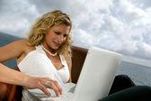 Mujer se sentó en la costa con el ordenador portátil — Foto de Stock