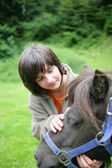 Boy caressing a pony — Stock Photo