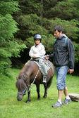 Vater seiner tochter ein pony reiten zu helfen — Stockfoto