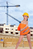 Beautiful half naked woman posing on a construction site — Stock Photo
