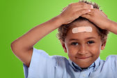 Coloured little boy with plaster on his forehead against fluorescent green — Stock Photo