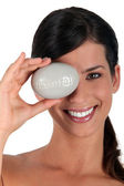 Woman covering eye with pebble marked natural — Stock Photo