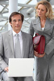 Man using a laptop computer accompanied by a woman with a red briefcase — Stock Photo