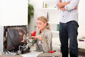 A female technician repairing a television — Stock Photo