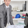 Stock Photo: Businessmlooking at architectural draw