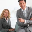Smiling executives with laptop computer — Stock Photo