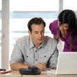 Couple at a desk with a laptop — Stock Photo #8581154