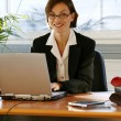 Businesswoman sitting at her desk — Stock Photo