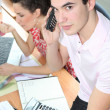 Young man on the phone whilst sitting on an office desk — Stock Photo