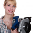 Stock Photo: Womholding circular saw