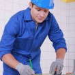 Young technician cutting a pipe — Stock Photo #8583602