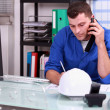 Construction foreman speaking on the phone - Stock Photo