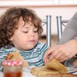Mother giving children breakfast - Stock Photo
