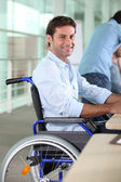 Man working in a wheelchair — Stock Photo