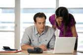 Couple at a desk with a laptop — Stock Photo