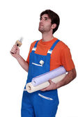 Handyman going to stick roll papers — Stock Photo