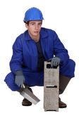 Worker holding a cinder block and trowel — Stock Photo