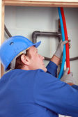 Plumber feeding hot and cold pipes behind a wall — Stock Photo