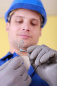 Plumber with a bracket for water pipes — Stockfoto
