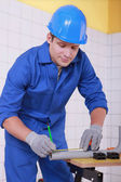 Young technician cutting a pipe — Stock Photo