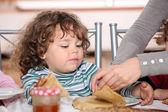 Mother giving children breakfast — Stock Photo