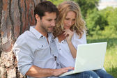 Couple in park on laptop computer — Stock Photo