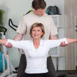 Stock Photo: Personal trainer helping his client with her posture