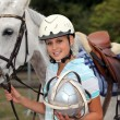 Professional female jockey posing with her horse - Stock Photo