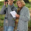 Senior woman and senior man watching through binoculars — Stockfoto