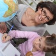 Mother teaching daughter geography — Stock Photo #8649061
