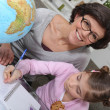 Stock Photo: Mother teaching daughter geography