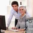 Young man and older woman using a computer — Stock Photo