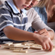 Young boy playing dominoes with his father — Stock Photo #8649339