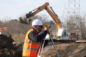Surveyor em canteiro de obras com guindaste em plano — Foto Stock